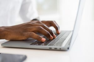 A Black man is utilizing a laptop. He is searching for online therapy in Georgia. Luckily, he found an online therapist in Georgia with Faith and Family Empowerment based in Norcross, Georgia.