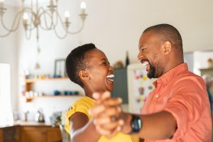 A couples dances and smiles at each other. They are pleased with the progress they have made in black marriage counseling in Atlanta, GA with Faith and Family Empower.
