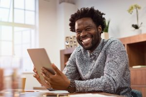 A man smiles while holding an iPad. He is pleased with his decision to begin anxiety treatment in Norcross with Faith and Family Empowerment near Atlanta, Georgia 30071.