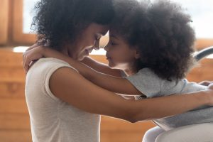 A mom and daughter share an embrace. They are feeling more in tune with faith after beginning Christian counseling in Atlanta, GA and online therapy in Georgia with Faith and Family Empowerment in Norcross, GA.