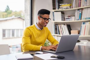 A man smiles while using his laptop for relationship therapy for singles in Atlanta, GA. He is feeling much better since he started relationship counseling for one with Faith and Family Empowerment in Atlanta, GA. You can get online therapy in Georgia here!