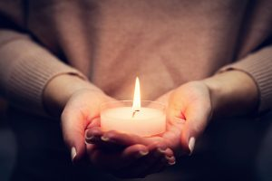 A person holds a candle. They have started grief counseling in Atlanta, GA with Faith and Family Empowerment, or in online therapy in Georgia with grief and loss online therapist William Hemphill.