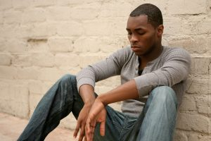 A young man sits on the ground leaned against a wall. He is having a hard time moving on from his loss and is starting grief counseling in Atlanta, GA with Faith and Family Empowerment. You can get help dealing with grief and loss with online therapy in Georgia too.