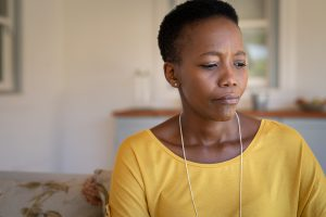 A woman sits on a couch looking anxious, She has has decided it's time to begin anxiety therapy in Atlanta, GA with Faith and Family Empowerment. You can get anxiety treatment in atlanta, ga with christian male counselor, William, an online therapist in Georgia
