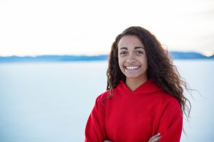 A young woman stands in front of a lake smiling. She has completed her journey through grief and loss with grief counseling in Atlanta, GA with Faith and Family Empowerment. She worked with online therapist in Atlanta, William, for online therapy in Georgia for grief and loss.