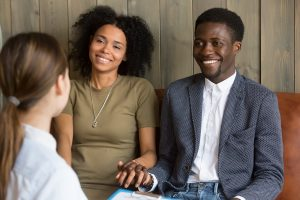 A couple smiles together while they work with a marriage counselor to help them in recovering from an affair. They get counseling for affair recovery in Atlanta, GA at faith and family empowerment 30071