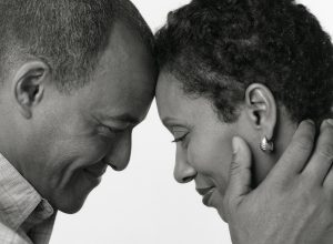 A couple stands with their faces touching. They are happy they started counseling for affair recovery in Atlanta, GA with Faith and Family Empowerment. They worked with a professional marriage counselor for help recovering from an affair.