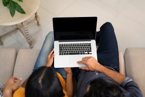 A couple uses a laptop together. They are scheduling their appointment for premarital counseling in Atlanta, GA with Faith and Family Empowerment. Their marriage counselors offer premarital counseling and online therapy for convince.