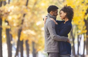 A couple embraces in the fall. They are feeling happy since starting counseling for affair recovery in Atlanta, GA with Faith and Family Empowerment 30071. A marriage counselor assists them in recovering from an affair.