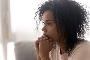 A girl sits alone looking worried. She is looking forward to beginning an anxiety support group in Atlanta, GA with Faith and Family Empowerment.