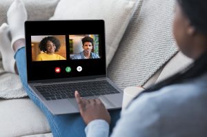 A person uses a laptop to start their online group therapy session. They are feeling much happier since starting depression support group in Atlanta, GA with Faith and Family Empowerment.