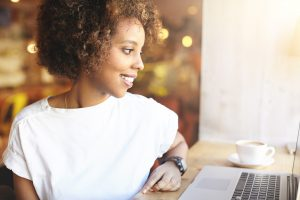 A woman smiles while using her laptop. She is feeling happy since starting an anxiety support group in Atlanta, GA with Faith and Family Empowerment.