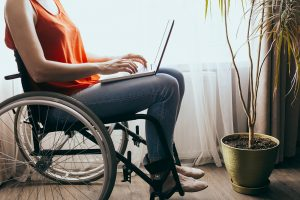A woman in a wheelchair uses her laptop to join her online group therapy session. She is feeling happier since starting depression support group in Atlanta, GA with Faith and Family Empowerment.